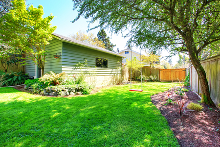 fenced: Fenced back yard with childs swing and green shed behind. View of well kept lawn and flower bed with stones