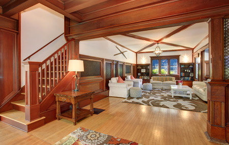 the vaulted: Luxury Living room interior with wooden walls, hardwood floor and vaulted ceiling. View of wooden staircase leading upstairs.. Stock Photo
