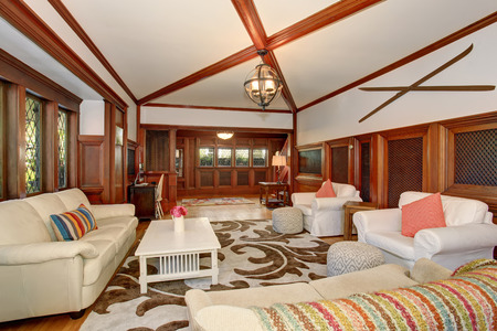 cherry hardwood: Luxury Living room interior with brown wooden trimmings, vaulted ceiling and beams. White sofa set and armchairs with pink pillows create comfort atmosphere.
