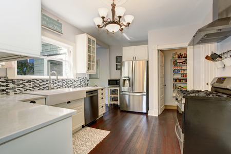 pantry: White kitchen room with stainless steel fridge and hardwood floor. View of a pantry.