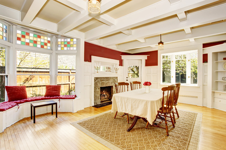sitting area: Bright dining room in red walls and white wooden trimmings. Also fireplace with stone decor and sitting area with wide window.