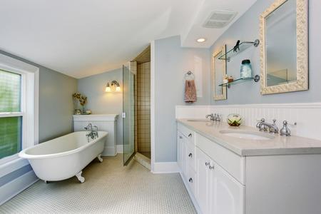 Elegante bagno in toni pastello blu con vasca da bagno bianca, armadi e doccia.