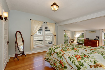 vaulted ceiling: Cozy bedroom interior with vaulted ceiling and hardwood floor. Furnished with brown cabinet and bed with floral bedding. Stock Photo