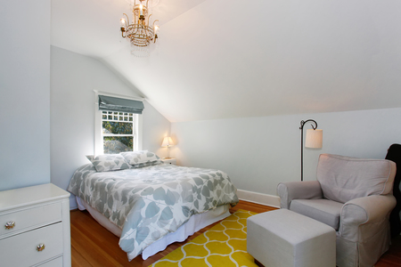 yellow walls: Cozy attic bedroom with white walls and yellow rug. Stock Photo