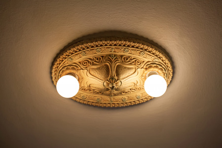 Vintage ceiling lamp close up on beige wall in empty  room.