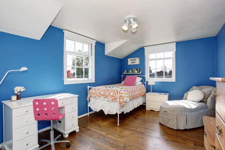 vaulted ceiling: Adorable blue kids room with hardwood floor and vaulted ceiling. Furnished with small iron bed, white desk with drawers and comfortable armchair.