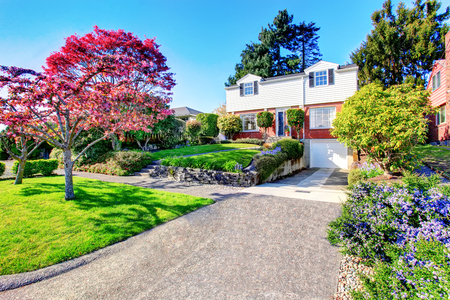 two level house: Beautiful curb appeal of two level house with one garage space. View of nice front garden landscape. Stock Photo