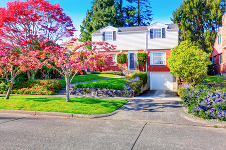 Beautiful curb appeal of two level house with one garage space. Also amazing front garden with red trees, flower beds and green lawn. Stock Photo
