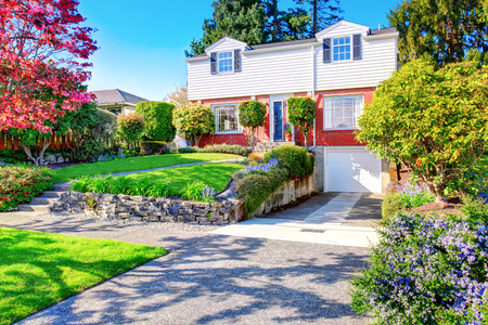 Beautiful curb appeal of two level house with one garage space. View of nice front garden landscape. Stock Photo
