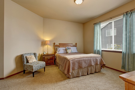 furnished: Elegant bedroom in soft colors with blue curtains and beige bed. Also carpet floor and creamy walls Stock Photo