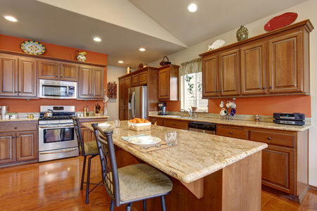 Brown kitchen room interior with granite counter tops and steel appliances. Vaulted ceiling and hardwood floor.