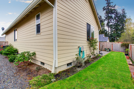 fenced: House exterior with beige siding. Fenced Back yard with green lawn and flower bed