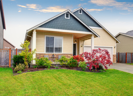 Beautiful curb appeal of sweet beige house with green front garden. View of porch with chairs.
