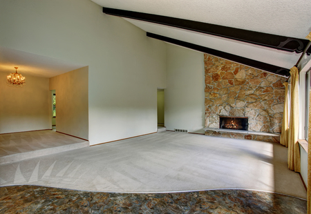 Spacious unfurnished living room interior with high vaulted ceiling and stone trim fireplace. Also has yellow curtains and beige carpet floor.