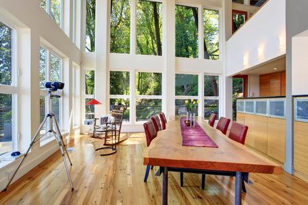 현대 호수 집 거실의 놀라운보기. 큰 나무 테이블과 빨간색 의자 제공.