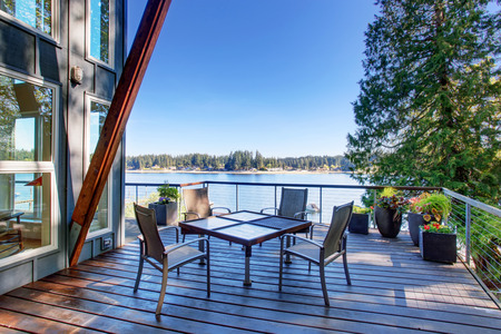 Large covered and furnished porch of luxury house with view of the lake. House exterior. Stock Photo