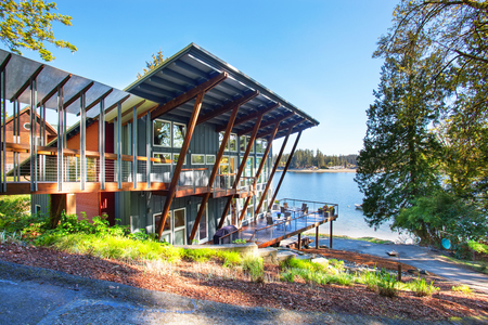lake house: Large covered and furnished porch of luxury house with view of the lake. House exterior. Stock Photo