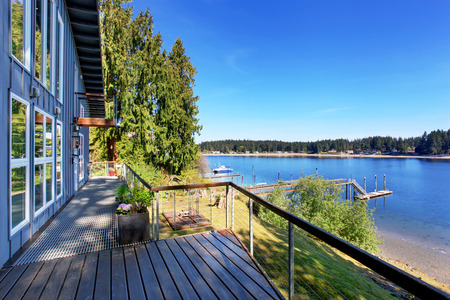 Walkout deck of luxurious home with an amazing view of lake. House exterior.