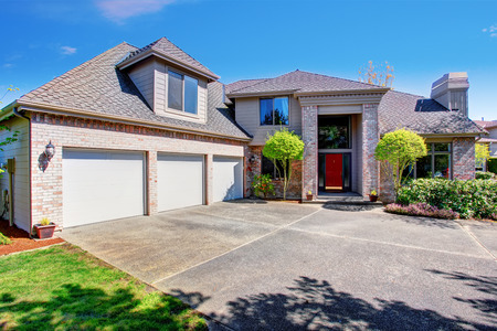 Groot modern huis met drie Garage en beton oprit. Uitzicht op een hoog plafond portiek met bakstenen muren