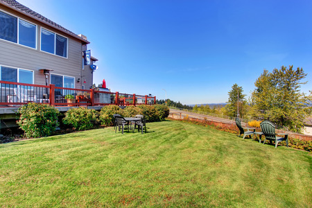 garden styles: Spacious back yard with grass filled garden and amazing view. House exterior.