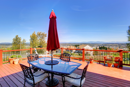 table and chairs: Wooden walkout deck with patio table, umbrella and chairs overlooking beautiful landscape