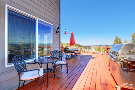 deck: Wooden walkout deck with patio table and barbecue overlooking beautiful landscape