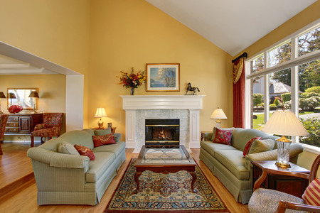 Elegant living room interior. Gray sofas with red pillows and white fireplace create comfort and cozy atmosphere