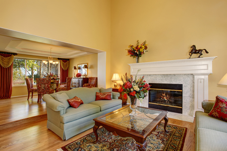 fireplace living room: Elegant living room interior with white fireplace and flowers. View of the dining room Stock Photo