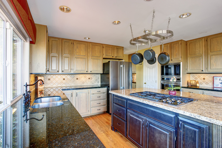 kitchen cabinets: View of modern kitchen room interior with kitchen island, stainless steel appliances and honey color cabinets.