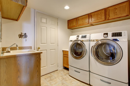 White laundry room interior with cabinets, sink and tile floor. House interior.
