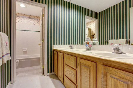 Nice bathroom interior in green tones with cabinets, double sink and tile floor.