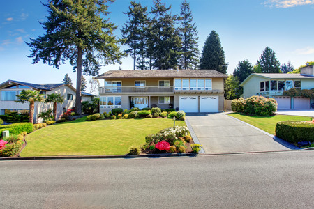 Beautiful curb appeal of two story house with beige exterior paint. Nice front garden with well kept lawn and trimmed hedges Stock Photo