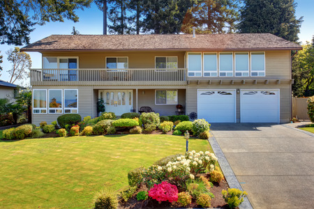 curb: Beautiful curb appeal of two story house with beige exterior paint. Nice front garden with well kept lawn and trimmed hedges Stock Photo