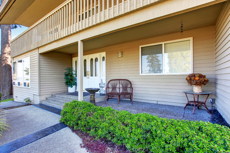 trimmed: View of cozy porch with concrete walkway and trimmed hedges.  House exterior. Stock Photo