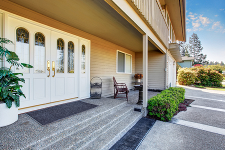 Spacious entrance porch with white Double front doors of luxury home. View of concrete walkway Stock Photo