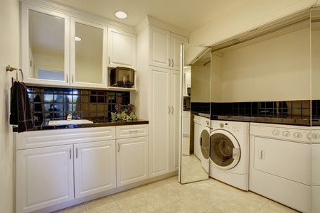 Small kitchen room with white cabinets and black back splash trim. Room has a built-in laundry area with washer and dryer Stock Photo