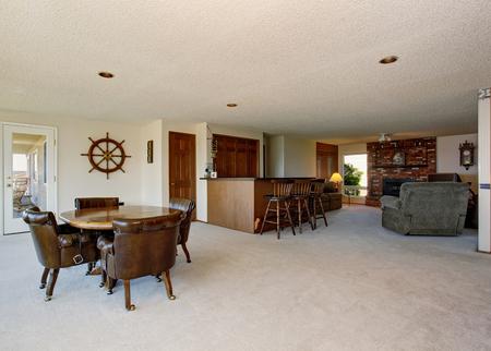 Plan de piso abierto en la casa de lujo. comedor con mesa y sillas de cuero marrón, sala de estar con chimenea de ladrillo. Foto de archivo