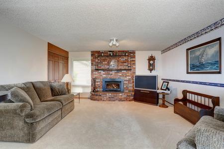 Cozy American living room with gray sofa, carpet floor and brick fireplace. 版權商用圖片