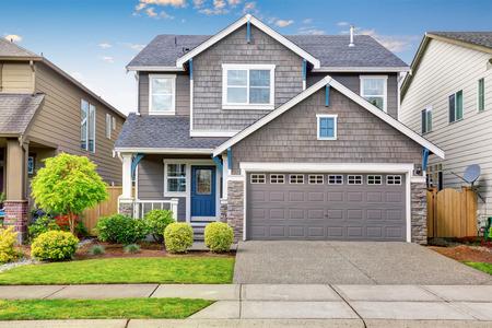 Agradable atractivo exterior de la casa de dos niveles, pintura moka Exter y calzada de hormigón. Vista del acogedor pequeño porche Foto de archivo