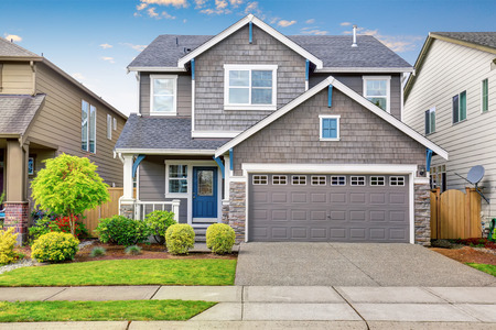 Nice curb appeal of two level house, mocha exterior paint and concrete driveway. View of cozy small porch Stockfoto
