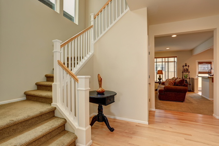Bright hallway in creamy tones with hardwood floor and staircase. View of living room.