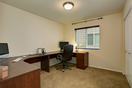 home office interior: Comfortable home office interior with large brown desk and laptops. Stock Photo