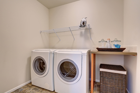 Small laundry room with white appliances and wicker basket. Has tile floor