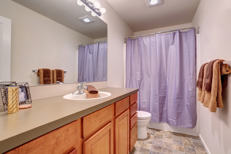 bathroom tile: Bathroom interior with modern cabinets, tile floor and lavender curtain. Stock Photo