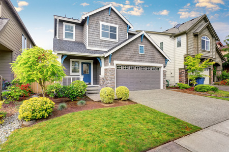 Nice curb appeal of two level house, mocha exterior paint and concrete driveway. View of cozy small porch Standard-Bild