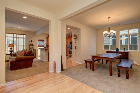 open floor plan: Open floor plan. View of dining room with Carved wooden table, living room with brown sofa and kitchen