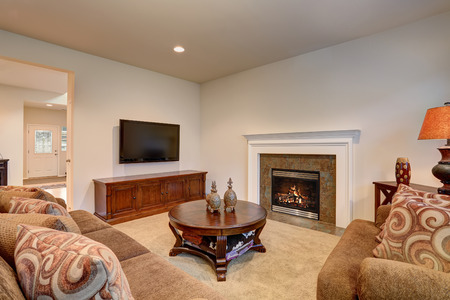 classic living room: Classic brown and white living room interior with carpet floor. View of fireplace decorated with tile trim.