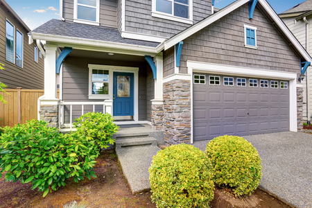 Nice curb appeal of two level house, mocha exterior paint and concrete driveway, trimmed bushes and green lawn