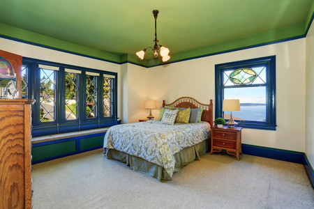 crater: Adorable antique bedroom interior with green ceiling and blue vintage stained glass window.