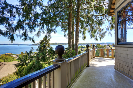 unfurnished: Large unfurnished porch with wooden railings of luxury house with water view. House exterior.